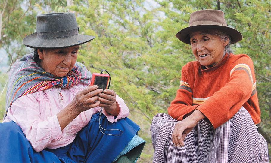 women in peru listen to the gospel on a solar powered