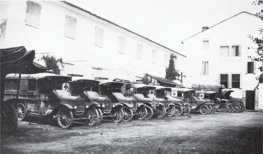 a row of red cross ambulances parked outside a hospital in italy